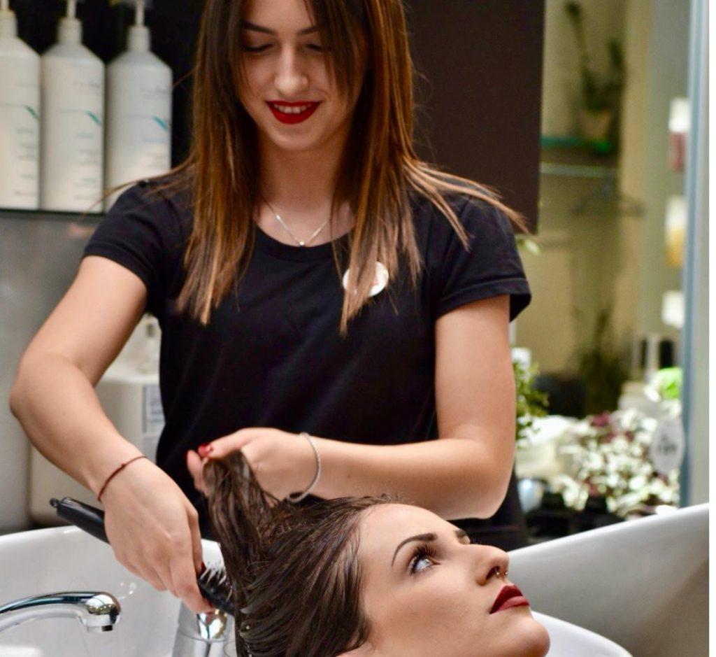 Giovane parrucchiera lava i capelli a una cliente