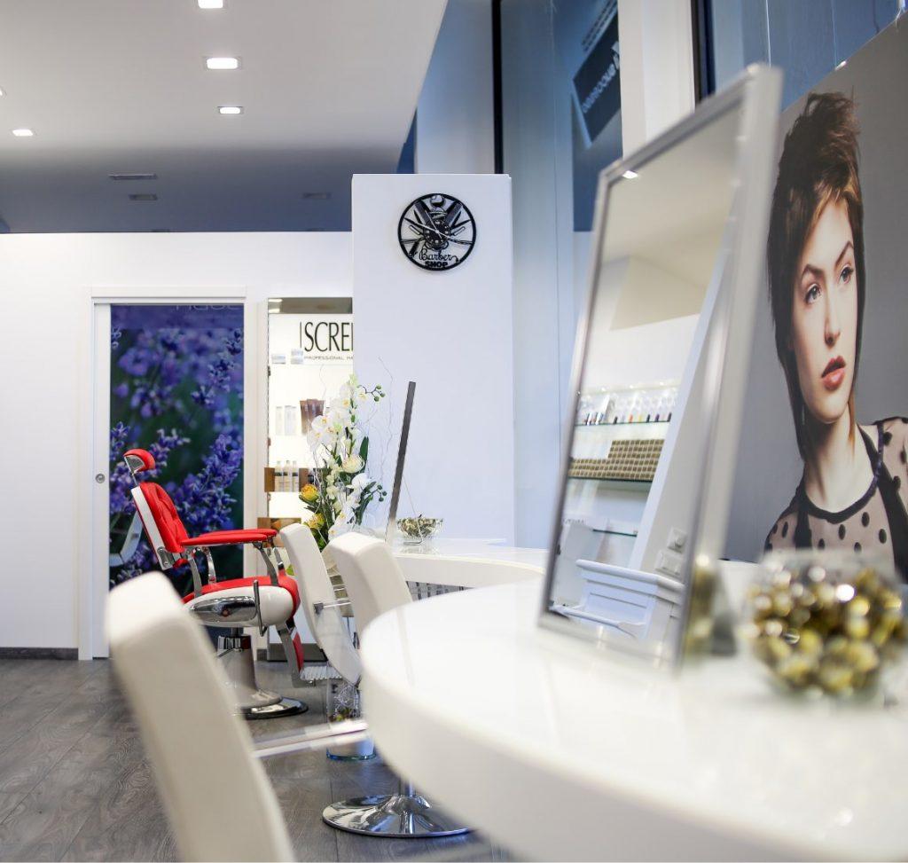 Interno di un salone di parruchiere con prodotti Screen e sedia da barbiere rossa