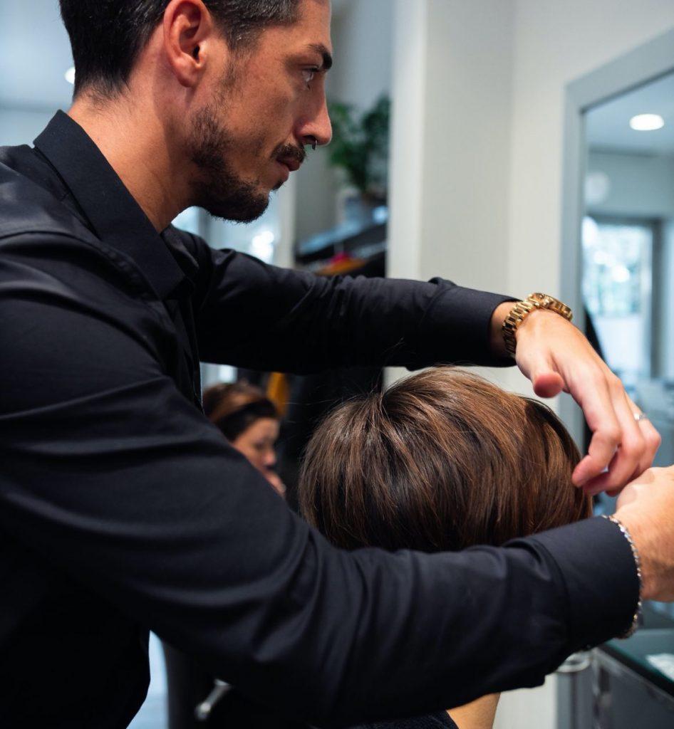 Parrucchiere nel suo salone che sta sistemando lo styling a una cliente